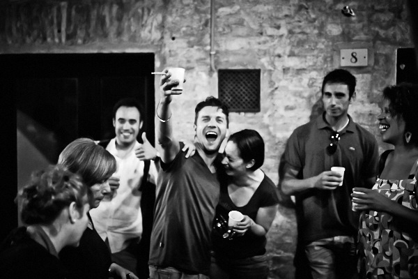 Fine art black and white photography of people in the street of Siena drinking wine after the Palio 2014