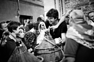 Black and white fine art photography of people in the street of Siena drinking wine after the Palio