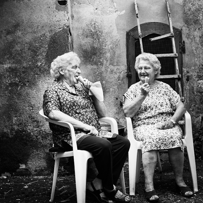 Fine art black and white image of two ladies in tuscany eating icecream