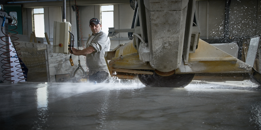 fine art corporate and industrial photography of a worker cutting a piece of marble in Italy