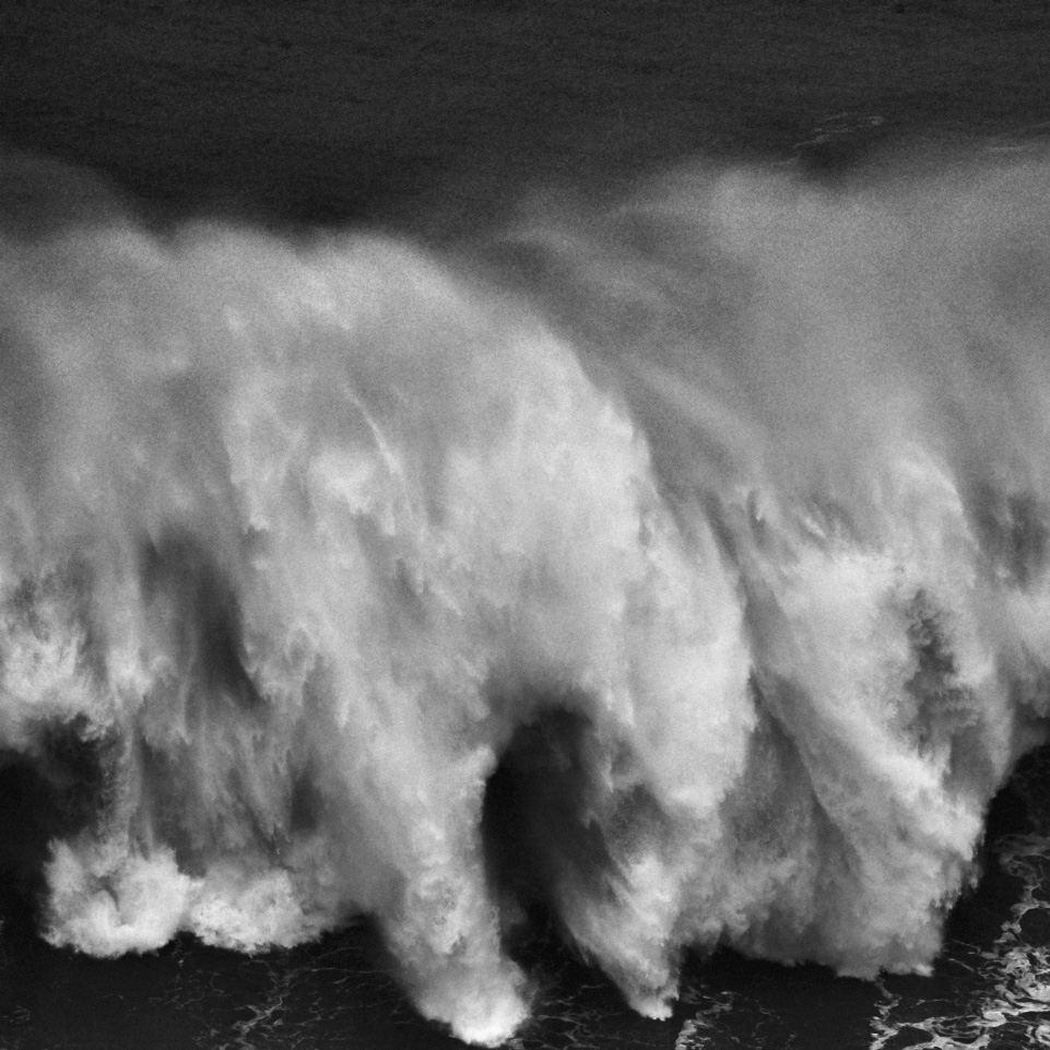 fine art black and white image of a big wave crashing in front of the lighthouse of Nazarè in Portugal