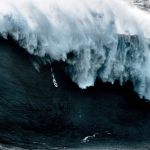 Fine art image of the atlantic ocean showing a surf board getting smashed by a huge wave in NAzaré