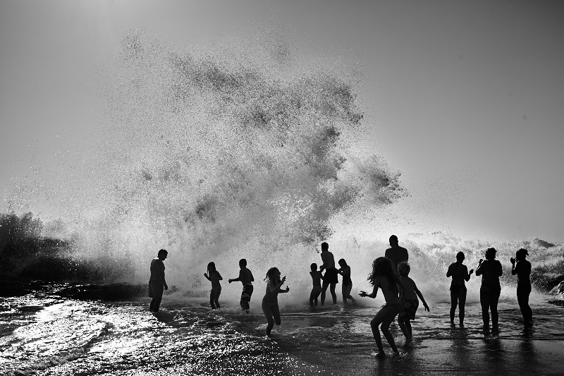 Fine art black and white photo of the ocean in Portugal with people enjoying it.