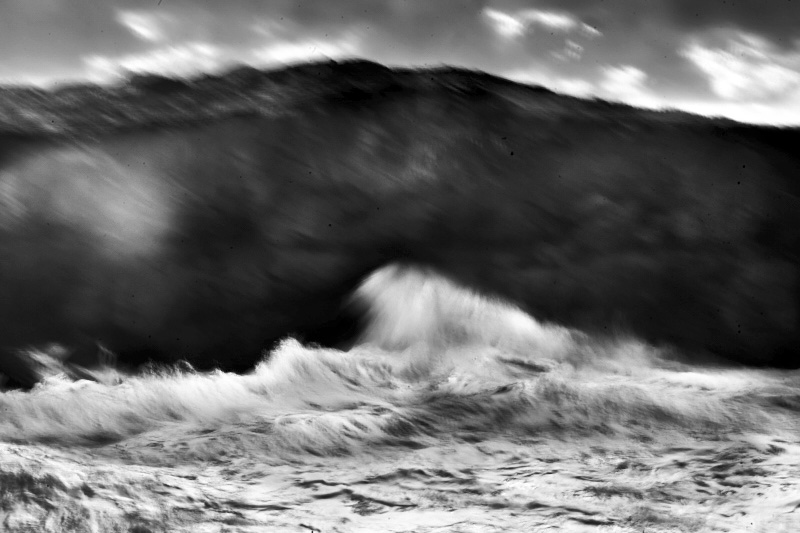 Fine art black and white image of an abstract view of the ocean smashing into a cliff in Portugal