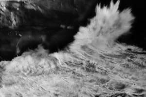 fine art black and white image of the ocean in Portugal. A wave breaking into a cliff