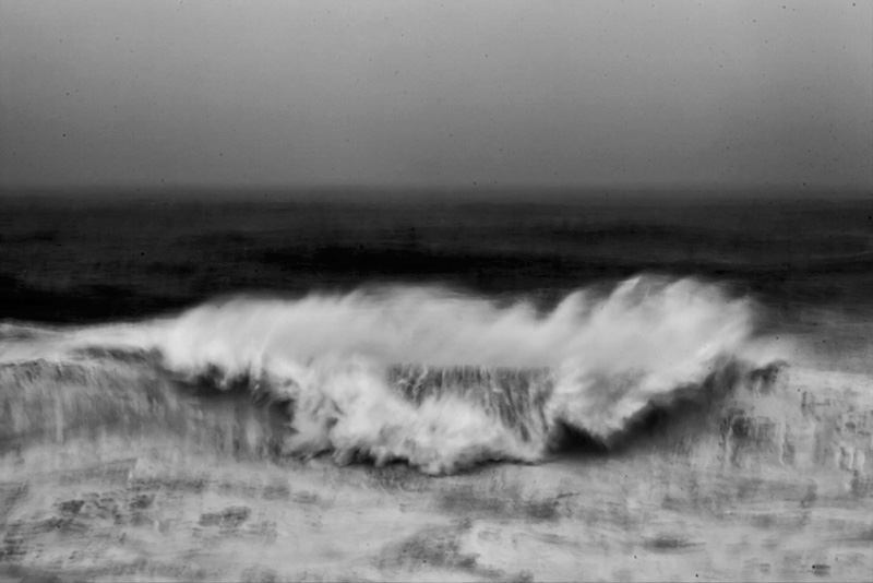 Fine art black and white image of an abstract view of the ocean smashing into a cliff in Portugal, Nazaré, north canyon. big wave surf