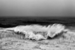 Fine art black and white image of an abstract view of the ocean smashing into a cliff in Portugal, Nazaré