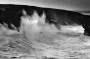 fine art black and white image of the ocean in Portugal. A wave breaking into a cliff in Sines, Alentejo, South Portugal