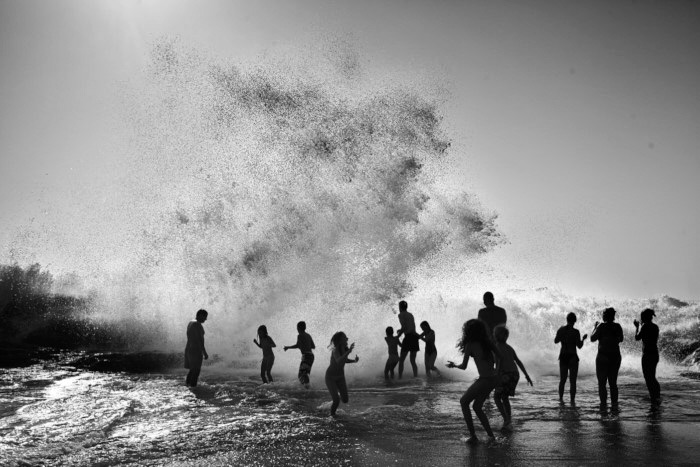 fine art image in blafine art image in black and white of people enjoying the ocean, awarded balck and white spider awardsck and white of people enjoying the ocean