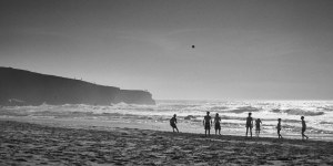 fine art black and white seascape of the atlantic ocean with people in front playing volley
