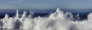 fine art photo of a big wave during a great swell closing in front of a cliff in praia do Malhào