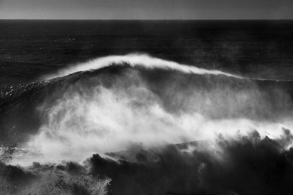 classic fine art black and white seascape of a huge wave in Nazaré, Portugal