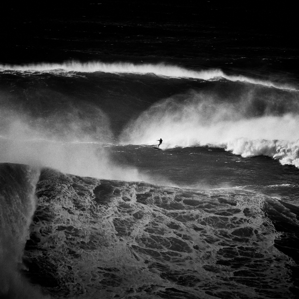 Fine art black and white image of a brazilan big wave surfer on a big wave in nazaré