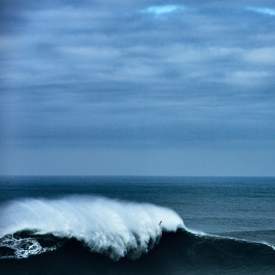 Fine art image of a surfer beaten by a giant wave in Nazarè during a huge swell along the Atlantic coast in Portugal